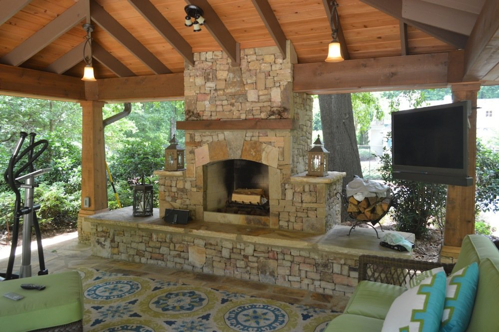 An outdoor fire place constructed of rough cut bricks is stationed under an outdoor covering.