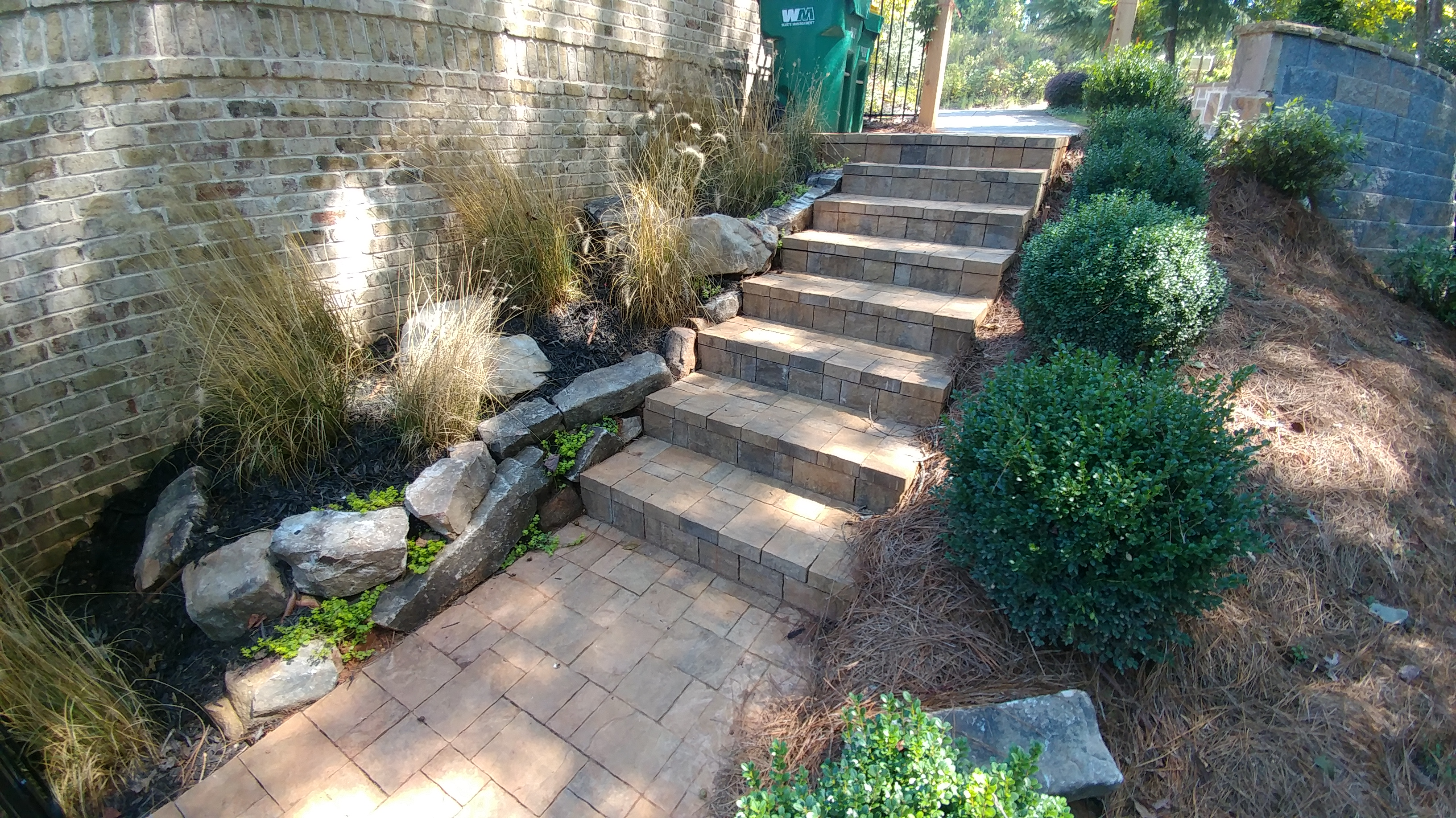 A set of stairs is made of carefully laid brick with tufts of well-manicured grasses lining the side.
