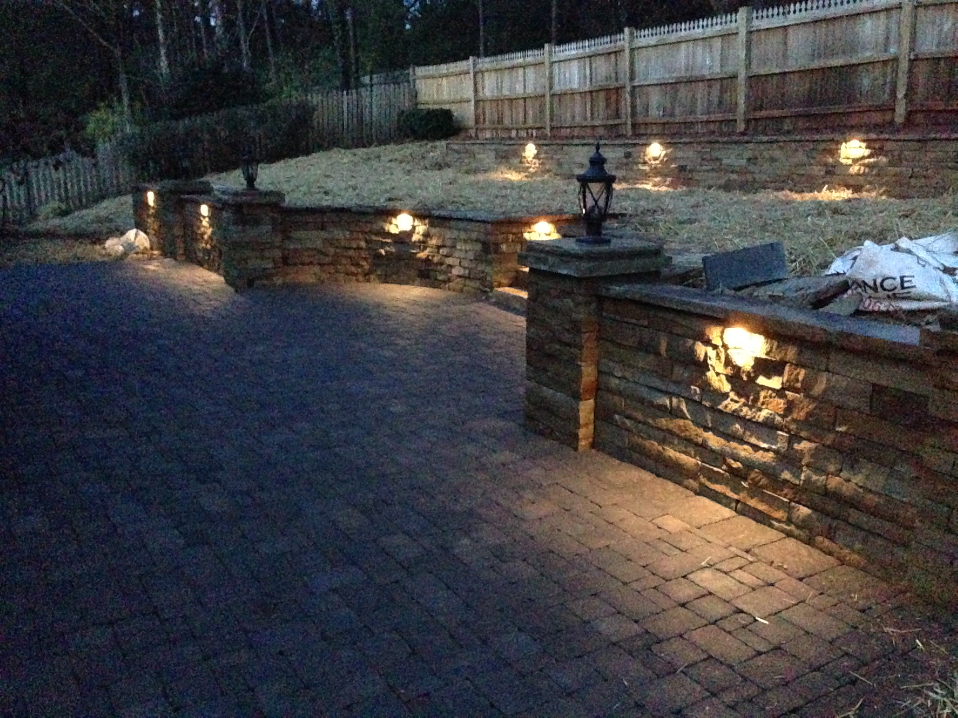 An all cobble patio is ringed in by a rough-hewn brick retaining wall.