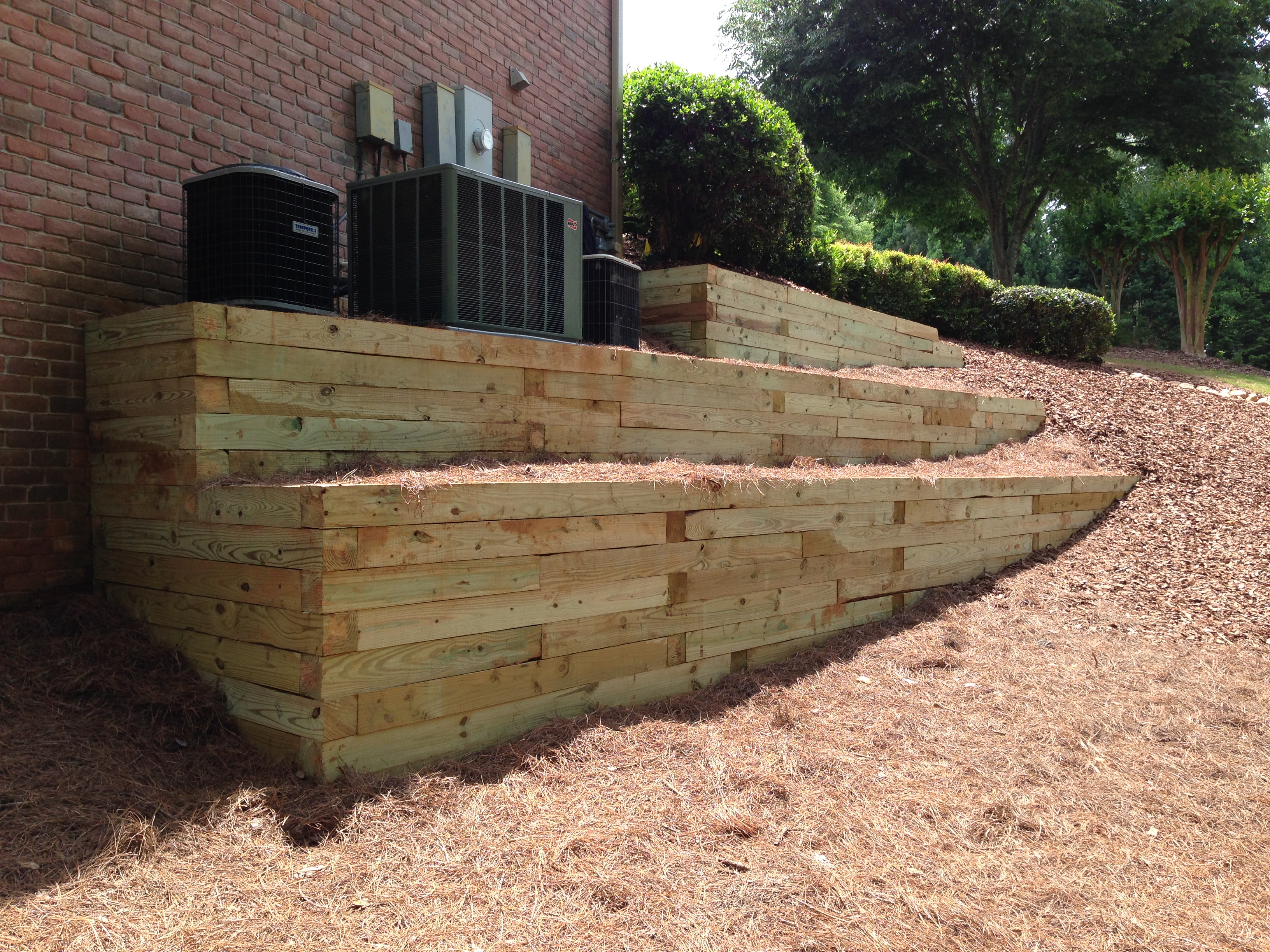 A series of retaining walls made of timber hold up the platform for heating and cooling units outside of a house.