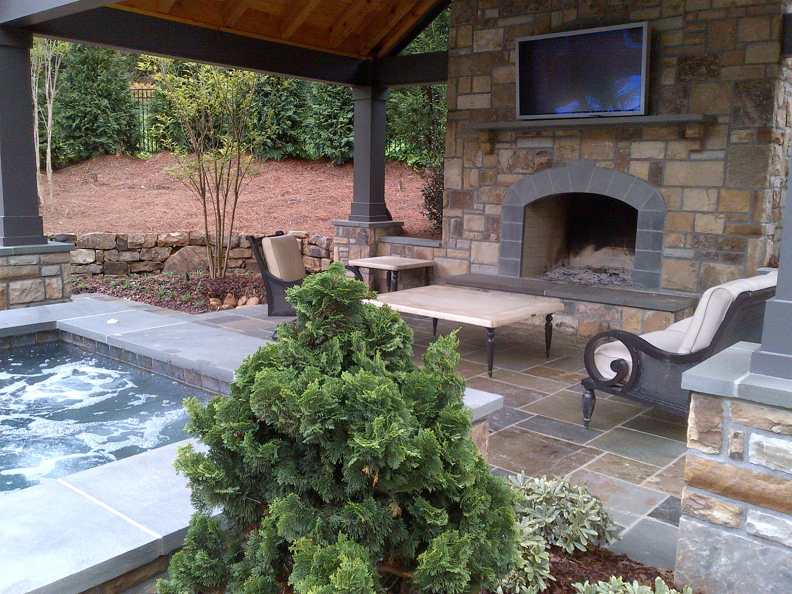 Outdoor stone fireplace with pool