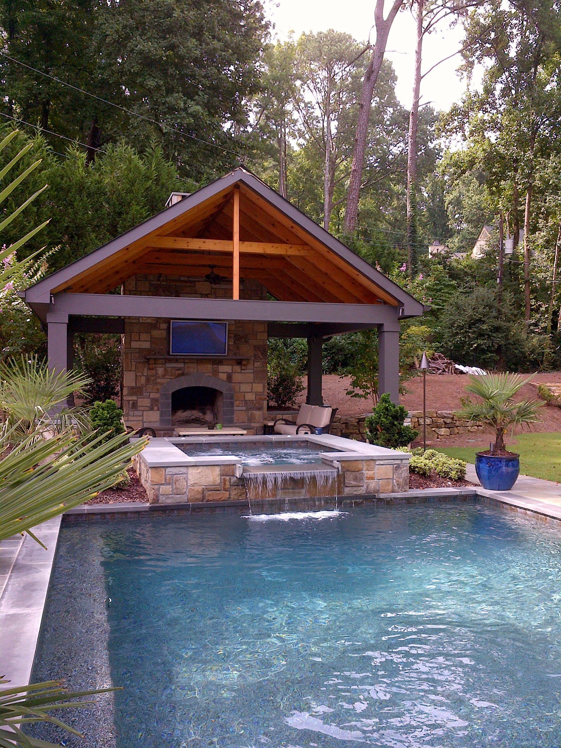 Pool and spa with a outdoor fireplace